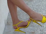 3 Walking around in yellow strappy high heel sandals.