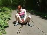 Redhead girl pees on the sidewalk