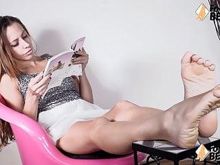 La ragazza scalza mostra gambe e piedi mentre legge un libro