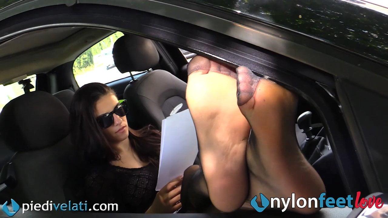 Heiße Brünette zeigt ihre Nylonfüße direkt auf der Straße